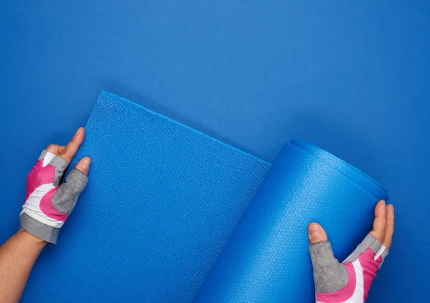 Two female hands in sports gloves unfold a blue yoga mat