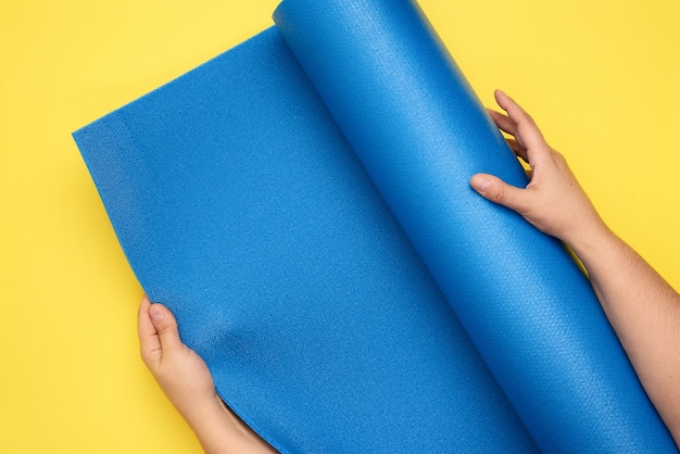 Two female hands unfold a blue yoga mat, top view