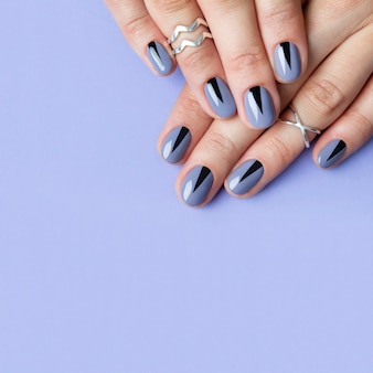 Two female hands with creative minimal manicure at purple table.