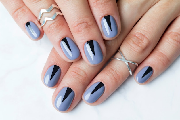 Two female hands with creative minimal manicure at white marble