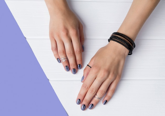 Two female hands with creative minimal manicure at white wooden table