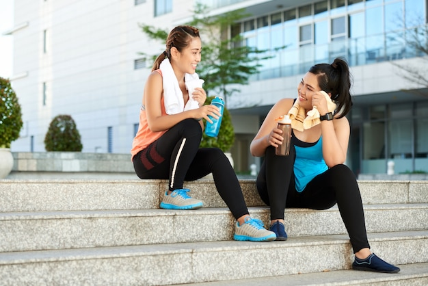 Two female joggers sitting on staircase with sports bottles and resting after workout