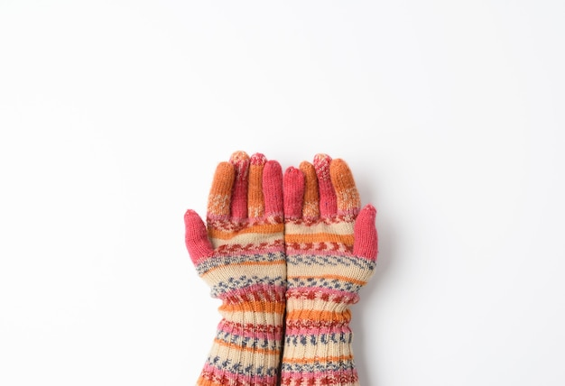 Two female joined palms in knitted multi-colored mittens on white, top view