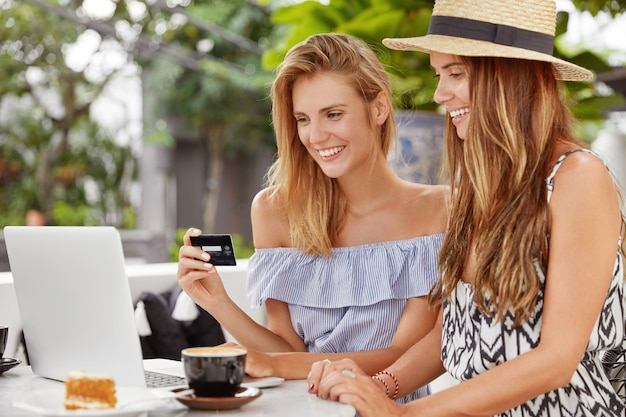 Two female lesbians spend leisure time together at coffee shop, work on laptop computer, make online shopping with credit card, look positively into screen, being satisfied with new purchase.