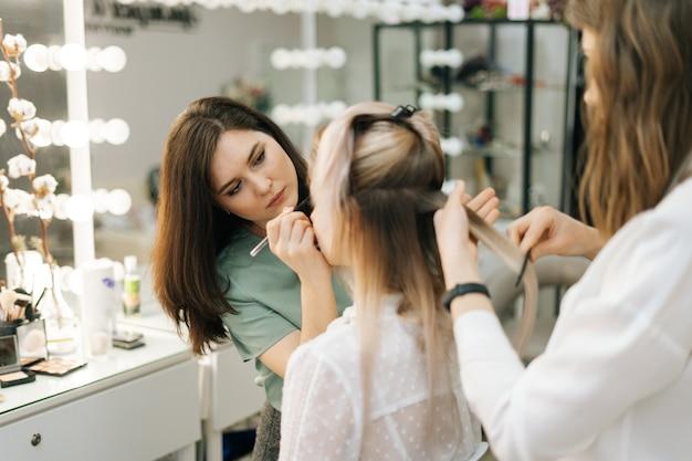 탈의실에서 젊은 여성 모델과 함께 일하는 두 여성 메이크업 아티스트