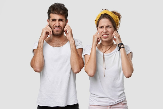Two female and male adults frown faces, plug ears as hear something unpleasant, wears casual outfit, isolated over white wall, ignore annoying sound