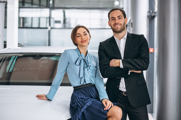 Two female and male salesperson at a car showroom