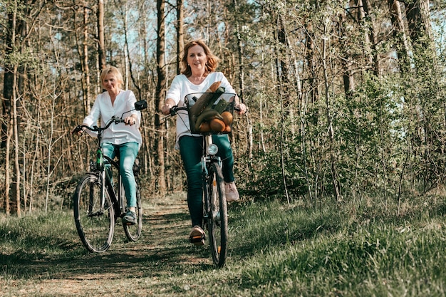 Two female mathure friends are riding bicycle bicycles through the forest. active lifestyle, hobby