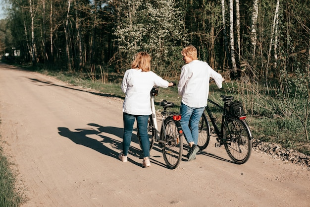 Two female mature friends are walking along the road with bicycles along the forest. back view