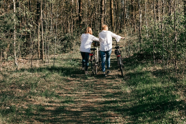 Two female mature friends are walking along the road with bicycles in forest. back view