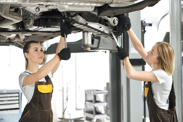 Two female mechanics repairing chassis of automobile