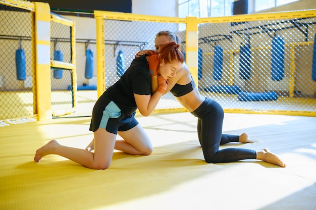 Two female mma fighters fights in a cage in gym.