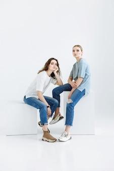 2人の女性モデルがカジュアルな服装で白いシーンの立方体に座っています