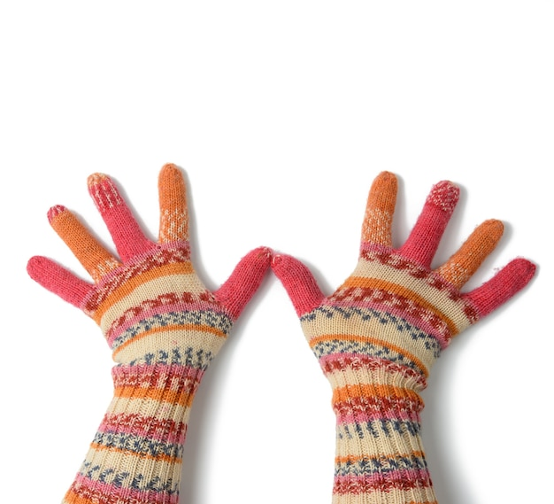 Two female palms in knitted multi-colored mittens on a white background, top view
