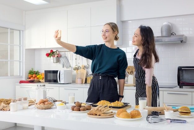 Две подруги веселятся, принимая селфи-завтрак на кухне.