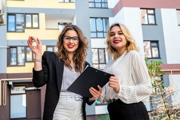 新しい家の近くの外に立っている2人の女性不動産業者が販売または賃貸の準備をしています