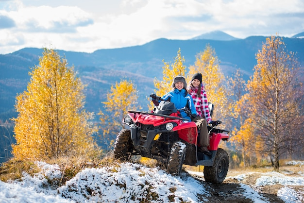Two female riders atv in jackets and hats on a snow-covered trail at sunny autumn day against trees with yellow leaves and mountains