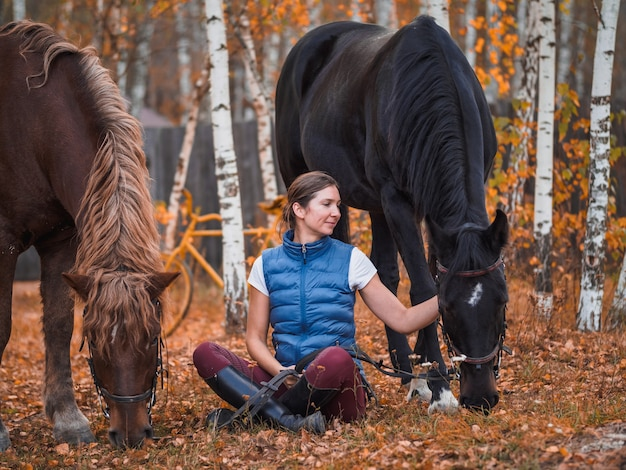 Two female riders sit on the grass next to the horses