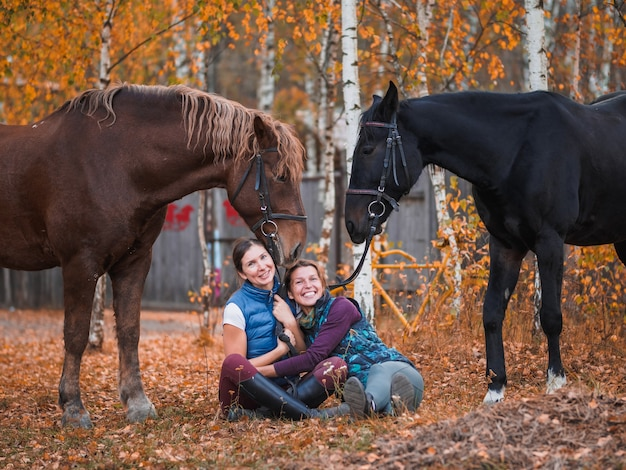 Two female riders sit on the grass next to the horses.
