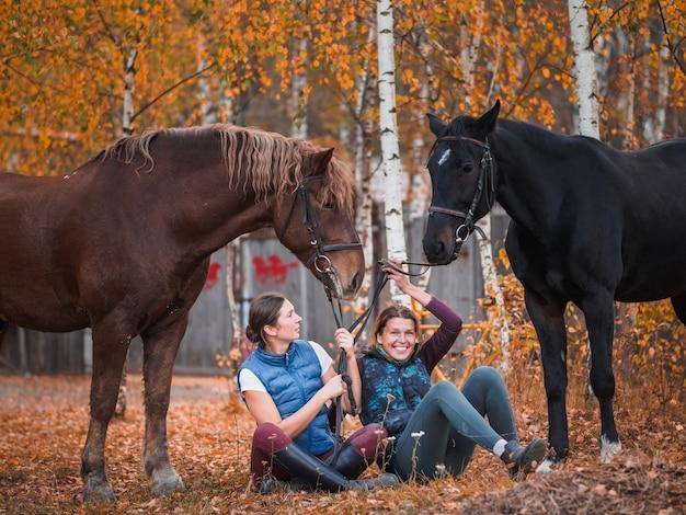 Две всадницы сидят на траве рядом с лошадьми.
