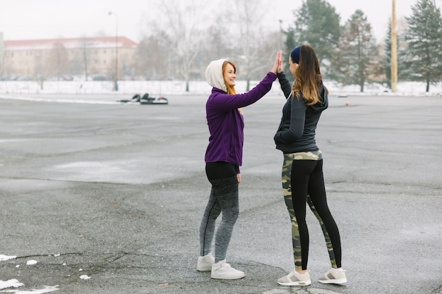 Two female runner standing on street giving high five