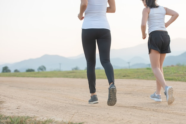 Two female runners jogging outdoors in forest in autumn nature.