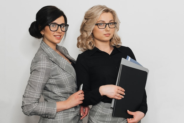 Two female secretaries on a light background
