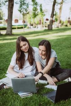 두 명의 여학생이 책과 노트북을 들고 잔디 공원에 앉아 공부하고 시험을 준비하고 있습니다. 원격 교육. 부드러운 선택적 초점입니다.