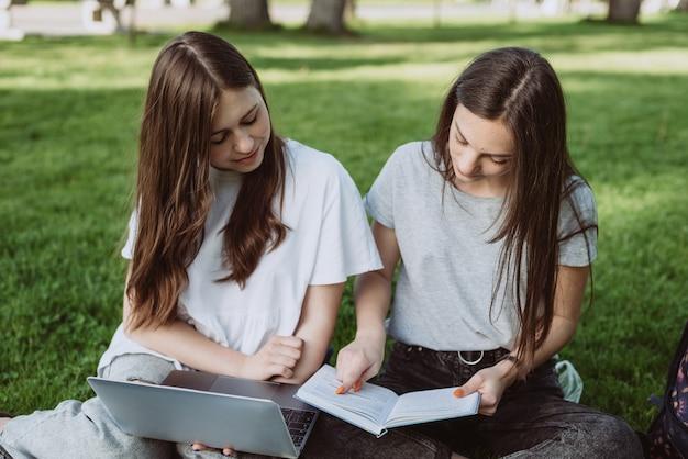 2人の女子学生が本とノートパソコンを持って芝生の公園に座って勉強し、試験の準備をしています。遠隔教育。ソフトセレクティブフォーカス。