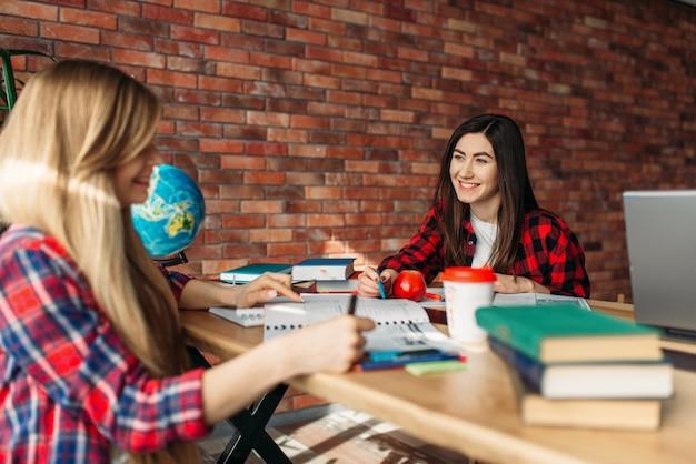 Две студентки вместе учатся за столом. люди готовятся к экзаменам, работа в команде в старшей школе