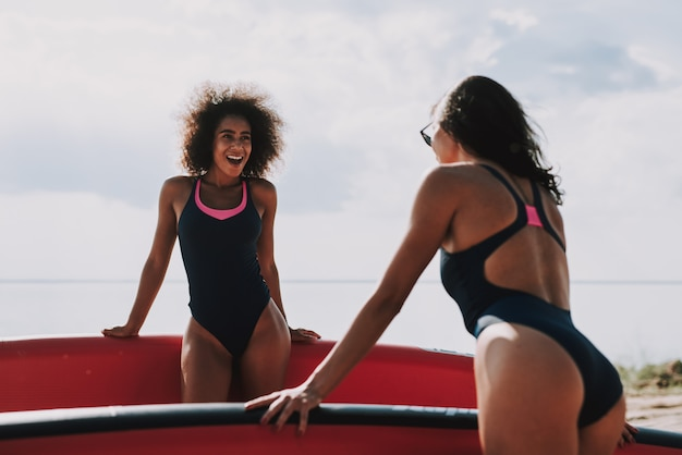 Two female surfers standing on beach in swimsuits.