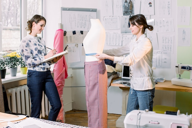 Two female tailors or seamstress taking mannequin measurements with measuring tape in fashion design studio, woman designer working with sketches in workshop, dressmaking and sewing concept