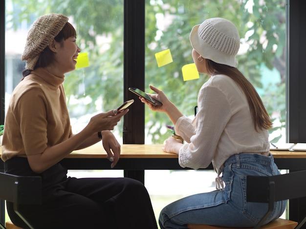 Две девушки-подростки держат смартфон и разговаривают друг с другом, сидя в кафе