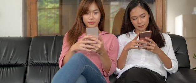 Две девушки-подростки сидят вместе на черном диване и используют смартфон в гостиной
