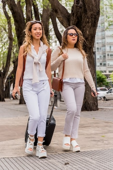 Two female tourist walking on city street with luggage bags