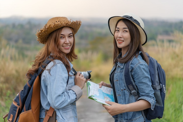 Two female tourist with backpack in countryside