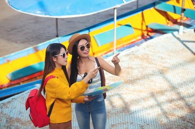 두 명의 여성 관광객이 장소를 찾기 위해지도를 들고 있습니다.