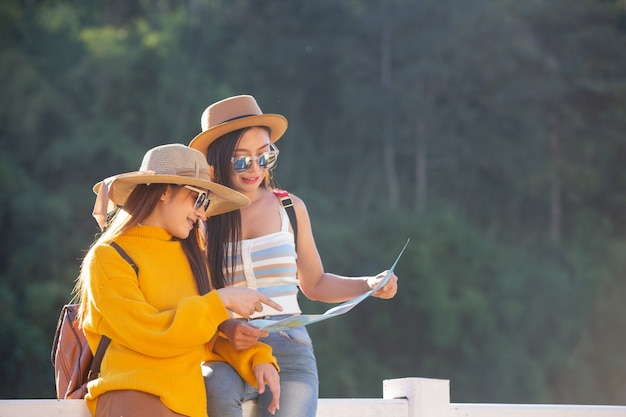 Two female tourists hold a map to find places.