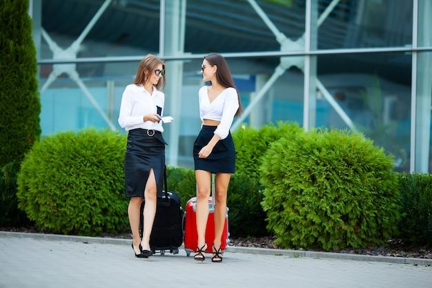 Две женщины-путешественницы гуляют со своим багажом возле аэропорта