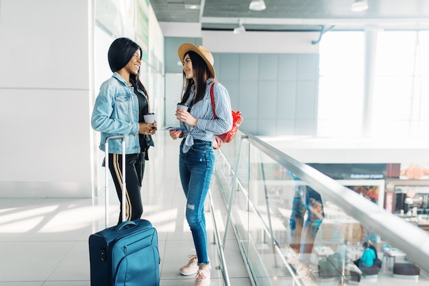 荷物を持った2人の女性旅行者が空港で旅行を始めます。エアターミナルに荷物をお持ちのお客様、背面図