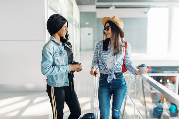 空港で荷物を持つ2人の女性旅行者