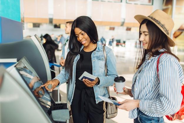 2人の女性旅行者が空港のatmで現金を引き出す
