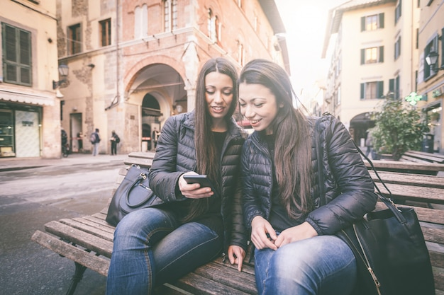 Two female twins looking at a smart phone