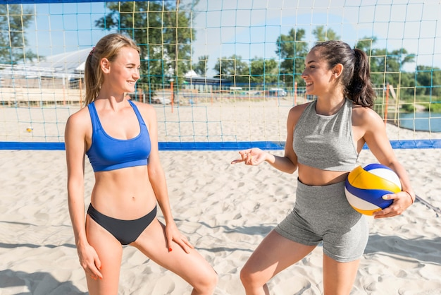 Two female volleyball players on the beach with net behind