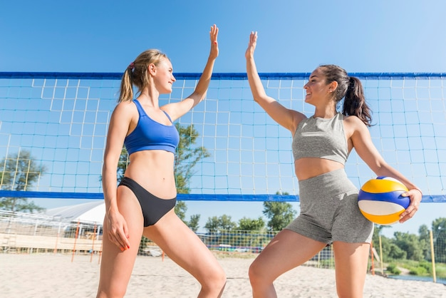 Two female volleyball players high-fiving each in front of net