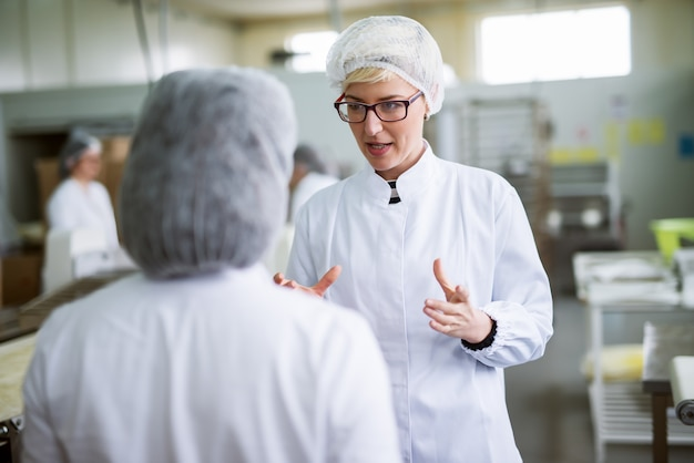 Two female workers discussing about food quality while standing in food factory.