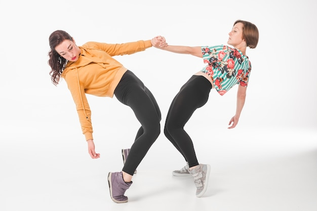Two female young woman dancing against white backdrop
