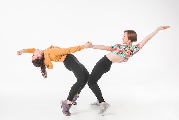 Una giovane donna di due femmine che tiene le sue mani che allungano