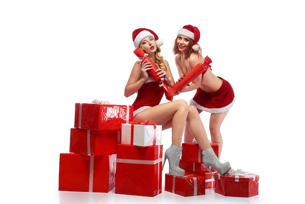Две женщины в рождественских костюмах, создавая около новогодних подарков.