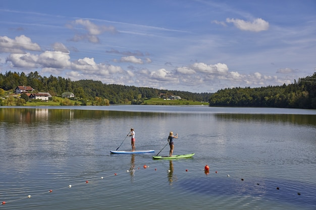 Due femmine in sella a uno stand up paddle board nel lago smartinsko in slovenia